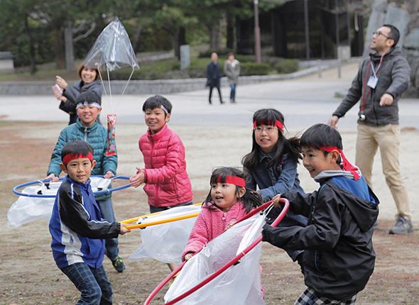 パラシュートにくくりつけてあるのは「うまい棒」。これを二人一組でキャッチする。(photo: Naoto Kakigami)