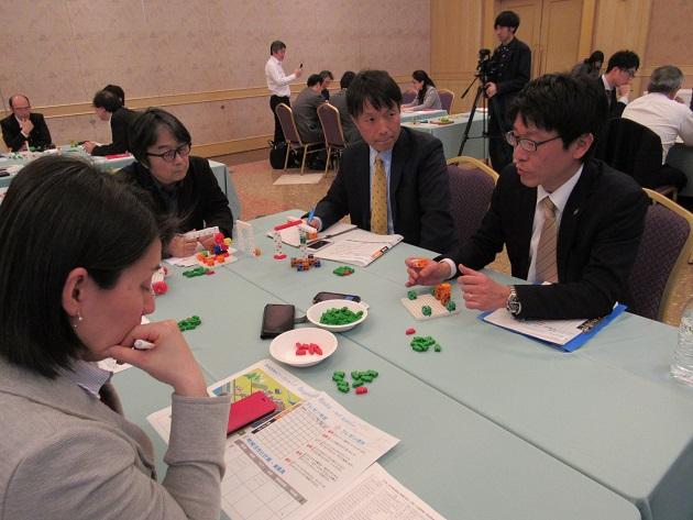 異なるチームのプレイヤーで構成されるテーブルで自身のアイデアを披露している参加者たち