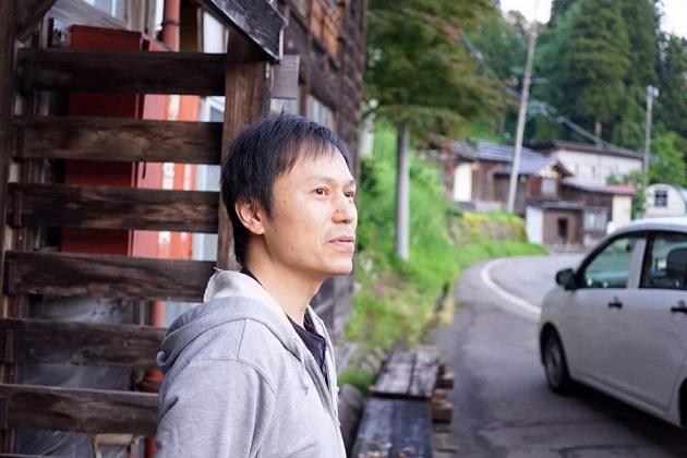 ギルドハウスの前に立つ西村さん
