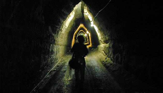 2002年夏、永昌寺トンネル内で撮影する中里さん。長さ142mのトンネル内に部分的に照明があり、それが光と闇の縞模様をつくっていて、なんだかタイムトンネルっぽい。(写真:中野純)