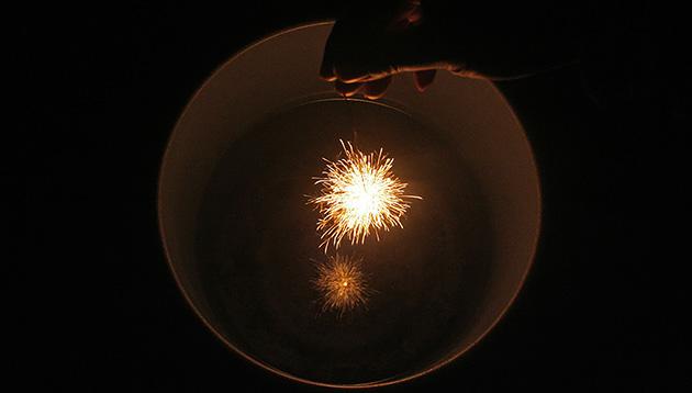 バケツに水を入れ、水に映る線香花火を同時に楽しむ。火花が松の枝葉のように四方に伸びるこのときを「松葉」と呼ぶ。