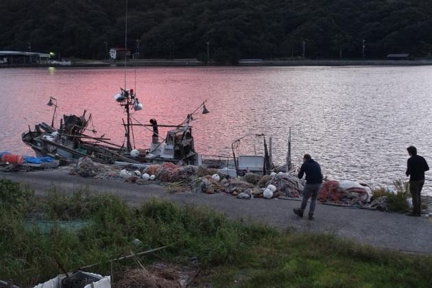 漁網と夕陽のコントラストが美しいと、夢中でシャッターを切るイギリス人ジャーナリスト。当たり前の風景も、外国人には新鮮に映るようだ(萩市江崎漁港)