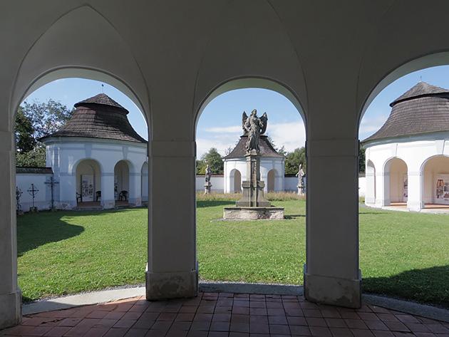 [上]Jan Blažej Santini Aichel (Giovanni Biagio Santini), Dolníhřbitov (Žďár nad Sázavou)入口にあたる小屋の窓から、中庭をのぞき込んだところ。4つの小さな小屋が、互いに伸ばした両手をつなぐようにして中庭をとり囲んでいる。(2017年9月、筆者撮影)