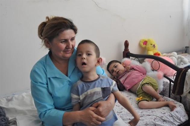 ケアワーカーと入院中の子どもたち。寝たきりの子も少なくない。言葉は通じないが、話しかけると答えてくれる。(写真:Tomo Odagiri)
